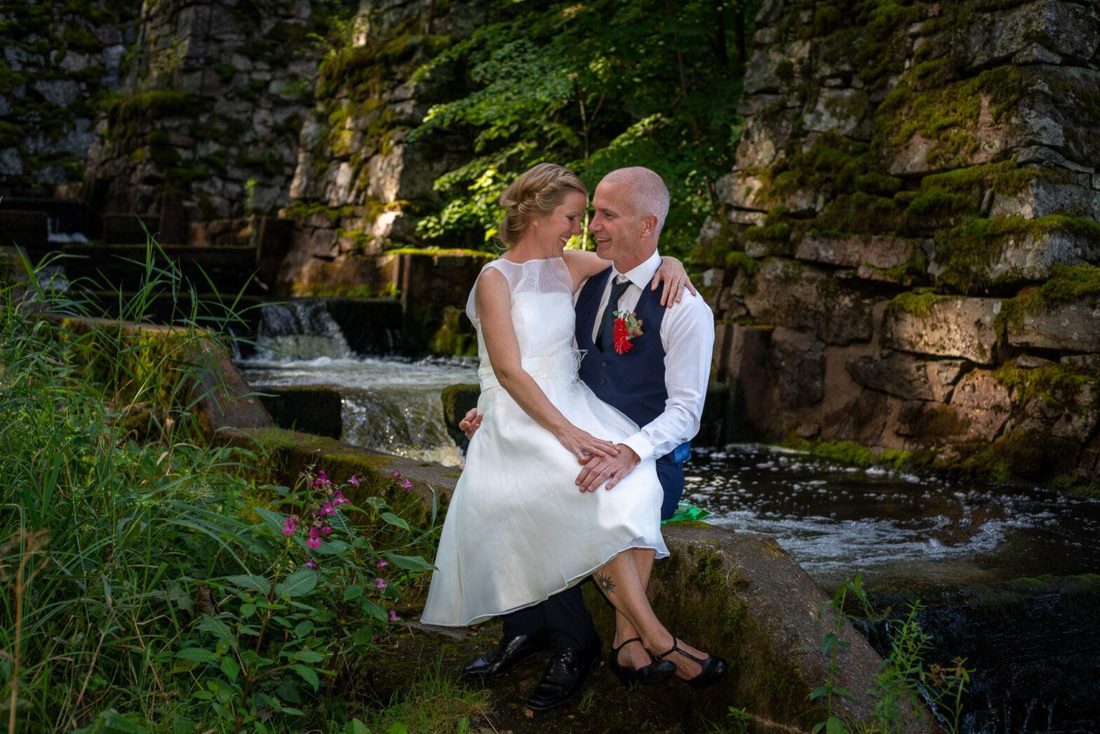 Bruden sitter i knät på brudgum vid laxtrappan i Älgå Arvika
