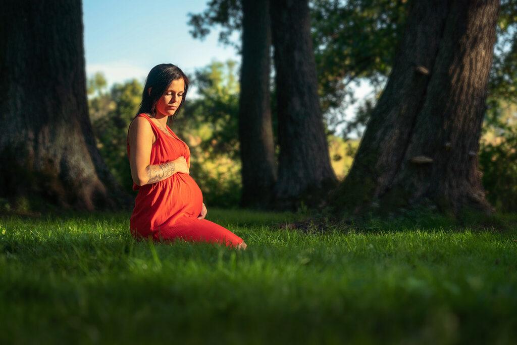 Gravid kvinna sitter på knä i röd klänning på gräset Sågudden Arvika