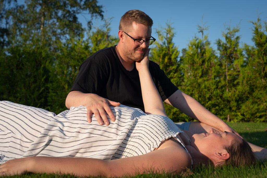 Gravid kvinna ligger på rygg och den blivande fadern sitter bredvid med handen på den gravida magen