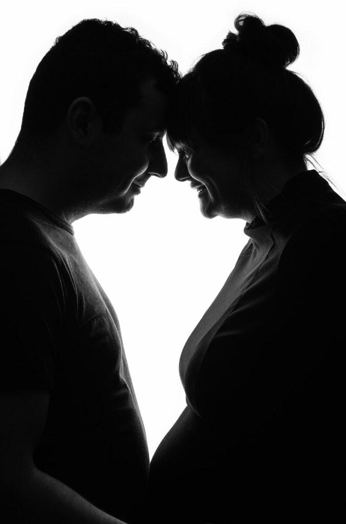 silhuett av blivande far och gravid mor i studio