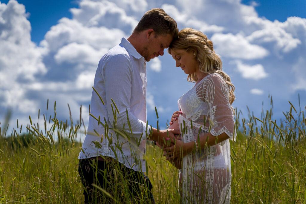 Blivande far och gravid mor står med huvuden mot varandra på en sommaräng