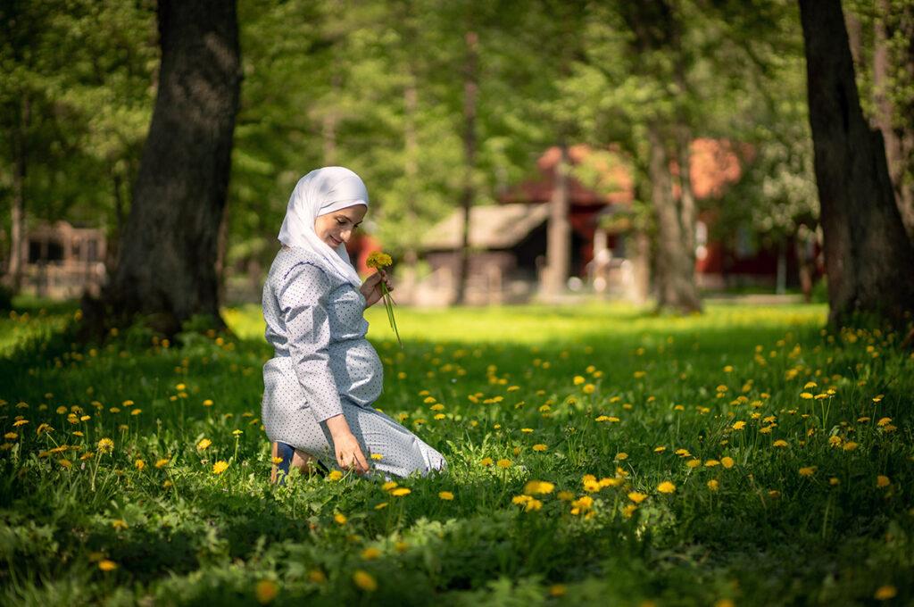 Gravid kvinna fullt påkläd sitter på knä i gräset och plockar maskrosor Sågudden Arvika