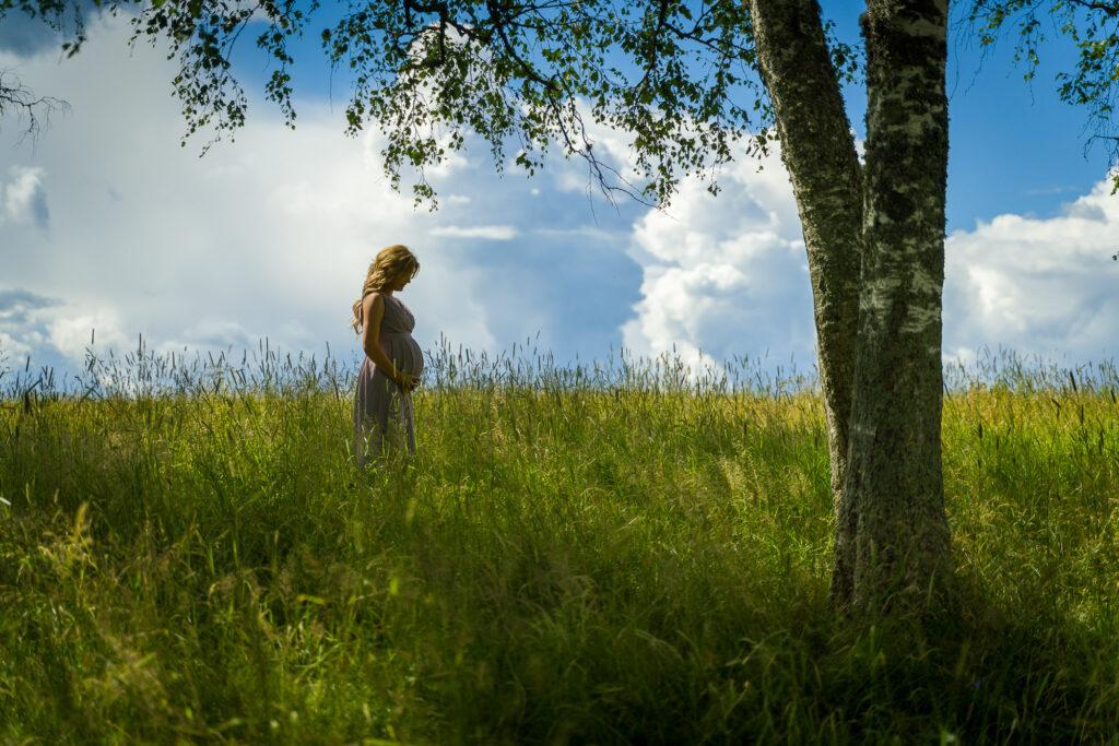 Gravidbild av kvinna som står på Sommaräng vid ett träd i Arvika