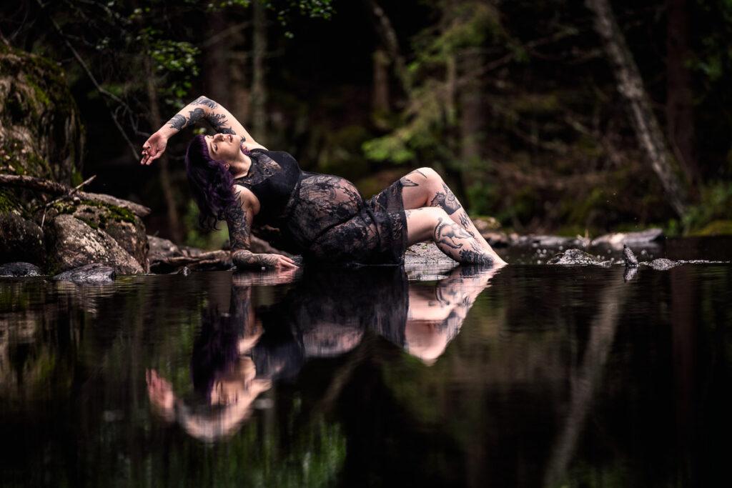 Gravid kvinna ligger vid damm i skogen och speglas i vattnet
